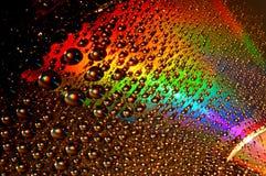 DVD- und CD-Diskette mit Wassertropfen färben Hintergrund Lizenzfreie Stockbilder
