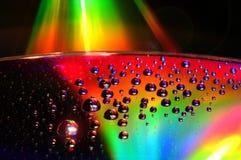DVD- und CD-Diskette mit Wassertropfen färben Hintergrund Lizenzfreie Stockfotografie