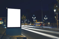 Аdvertising mock up banner in metropolitan city. Illuminated blank billboard with copy space for your text message or content, public information board in night Stock Images