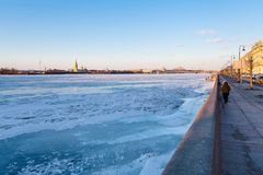 Dvortsovaya Embankment along frozen Neva river. And view of Peter and Paul Fortress in Saint Petersburg city in March evening Royalty Free Stock Image
