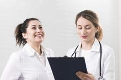 Dwa żeńskiego asystenta opowiada do siebie w dentystyki centrum ubierali w białych żakietach obrazy royalty free