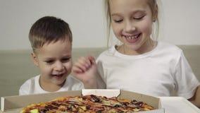 Dwa ślicznego dziecka w białych koszulkach, chłopiec i dziewczynie, otwierają pudełko pizza i cieszą się fundę zbiory