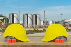 Dwa Żółty Zbawczy hełm na drewnie z rafineria ropy naftowej przemysłem z Obraz Royalty Free