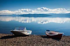 Dwa łódź na jeziornym brzeg Zdjęcia Royalty Free