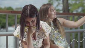 Dwa ładnego żeńskiego ucznia siedzi outdoors wpólnie Jeden dziewczyna słucha muzyka z jej hełmofonami, po drugie jeden zbiory