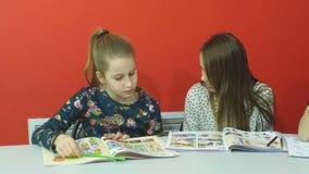 Dwa ładnego przyjaciela dyskutuje coś w copybook przy lekcją zbiory
