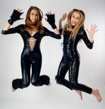 Dwa ładnej dziewczyny w kotów kostiumów skakać obrazy royalty free