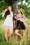 Dwa ładnej dziewczyny w ogródzie pod drzewem zdjęcie royalty free