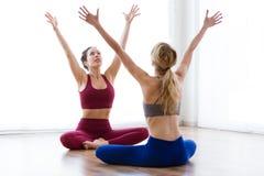 Dwa ładnej młodej kobiety ćwiczy joga w domu Zdjęcia Stock