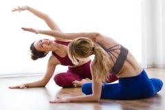 Dwa ładnej młodej kobiety ćwiczy joga w domu Obraz Stock