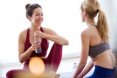 Dwa ładnej młodej sporty kobiety relaksuje po joga sesi w domu Zdjęcie Royalty Free