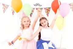 Dwa ładnej małej dziewczynki podczas przyjęcia urodzinowego zdjęcia stock