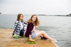 Dwa łyżwiarki rozochocona szczęśliwa dziewczyna w modnisia stroju ma obsiadanie na drewnianym molu podczas wakacje obrazy stock