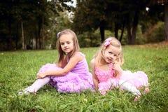 Dwa śliczna dziewczyna w pięknych sukniach jest roześmiana w sumie Obrazy Stock