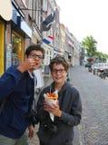 Dwa ślicznego dzieciaka z eyeglasses jedzą francuskich dłoniaki fotografia royalty free