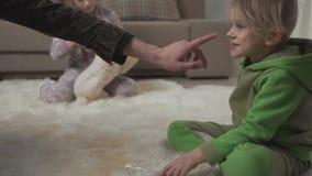 Dwa ślicznego dziecka kłaść na puszystym dywanie na podłodze bawić się z zabawkami w domu Męska ręka dotyka nos a zbiory