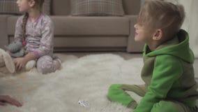 Dwa ślicznego dziecka kłaść na puszystym dywanie na podłodze bawić się z zabawkami w domu Męska ręka robi bałaganowi na chłopiec zbiory