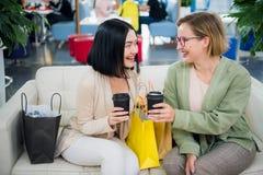 Dwa ślicznego dziewczyna spaceru w centrum handlowym z prezentem zdosą Szczęśliwy i ono uśmiecha się po robić zakupy z mnóstwo za fotografia royalty free