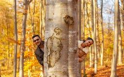 Dwa ślicznego kochanka ono uśmiecha się za drzewem zdjęcia royalty free