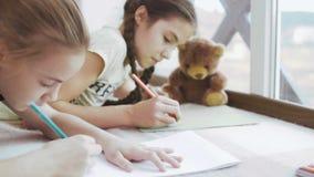 Dwa ślicznej dziewczyny rysują i relaksują na podłoga zbiory wideo