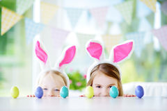 Dwa ślicznej małej siostry jest ubranym królików ucho bawić się jajecznego polowanie na wielkanocy Fotografia Royalty Free