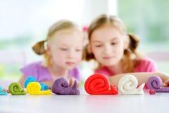 Dwa ślicznej małej siostry ma zabawę wraz z modelarską gliną przy daycare Kreatywnie dzieciaki pleśnieje w domu Dziecko sztuka z  Obraz Royalty Free