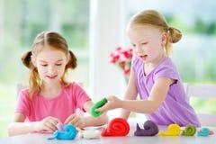 Dwa ślicznej małej siostry ma zabawę wraz z modelarską gliną przy daycare Kreatywnie dzieciaki pleśnieje w domu Dziecko sztuka z  Zdjęcie Royalty Free