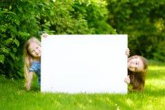 Dwa ślicznej małej siostry trzyma dużego pustego whiteboard na pogodnym letnim dniu outdoors Obrazy Stock