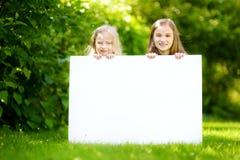 Dwa ślicznej małej siostry trzyma dużego pustego whiteboard na pogodnym letnim dniu outdoors Zdjęcie Royalty Free