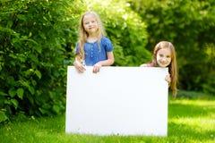 Dwa ślicznej małej siostry trzyma dużego pustego whiteboard na pogodnym letnim dniu outdoors Obraz Stock