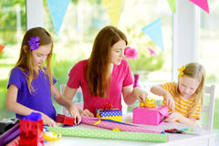Dwa ślicznej siostry i ich potomstwa matkują opakunkowych prezenty w kolorowym opakunkowym papierze Zdjęcia Stock