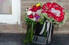 Dwa ślubny bukiet czerwone róże, inny kolorowy telefon komórkowy i kwiaty i obraz royalty free