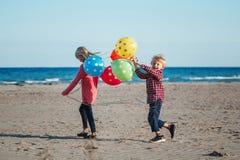 Dwa śmiesznego białego Kaukaskiego dziecko dzieciaka z kolorową wiązką balony, bawić się biegać na plaży na zmierzchu, jesieni la zdjęcie stock