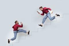 Dwa śmiesznego bliźniaczego mężczyzna biega w górę i na dół z książkami obrazy royalty free