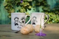 Dwa śmiesznej filiżanki z child& x27; s rysunki na stole Świeża babeczka na talerzu Herbata pije po środku słonecznego dnia Fotografia Royalty Free