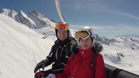 Dwa Śmiesznej narciarki Błaź się Wokoło Siedzieć Na Narciarskim dźwignięciu W zimy górze zbiory wideo