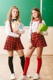 Dwa śmiesznej uczennicy w mundurku szkolnym stoją z książkami na tle zarząd szkoły fotografia stock