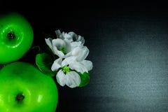 Dwa świeżego babcia kowala zieleni jabłka z kwiatami zamykają up na czarnym odbijającym tle, odgórny widok Zdjęcie Royalty Free