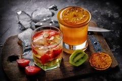 Dwa świeżego lata cocktailes z lodem na grunge kuchennym stole robić piec na grillu owoc, truskawki i kiwi pomarańczowy biały win Zdjęcia Stock