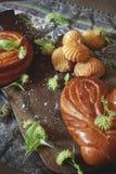 Dwa świeżej babeczki z ciastkami, kwiaty i mąka na tnącej desce obraz stock