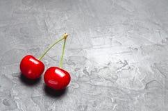 Dwa świeżej dojrzałej czerwonej wiśni na szarości betonują tło, lato jagoda minimalista miejsce tekst zdjęcia royalty free