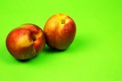 Dwa świeżej nektaryny na jaskrawym - zielony tło Obraz Stock