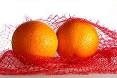 Dwa świeżej pomarańcze w siatka worku Zdjęcia Stock