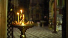 Dwa świeczki w kościół na candlestick na plamy kościelnym tle wśrodku zdjęcie wideo