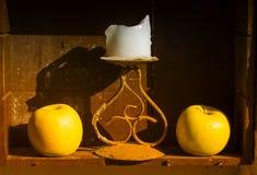 Dwa żółtej świeczki i jabłka obraz stock