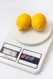 Dwa żółtej cytryny na białej kuchennej cyfrowej skala Obrazy Stock