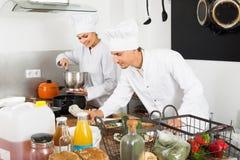 Dwa żeński i męscy młodzi kucharzi Zdjęcie Stock