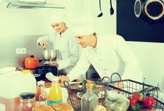 Dwa żeński i męscy młodzi kucharzi Obraz Stock