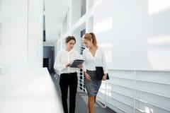 Dwa żeńskiego dyrektora dyskutuje pomysły projekt na cyfrowej pastylce podczas gdy chodzący w dół w biurowej sala, Obrazy Royalty Free