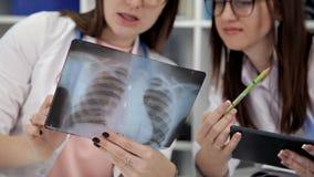 Dwa żeńskiego kobieta lekarza medycynego patrzeje promieniowania rentgenowskie w szpitalu zbiory wideo